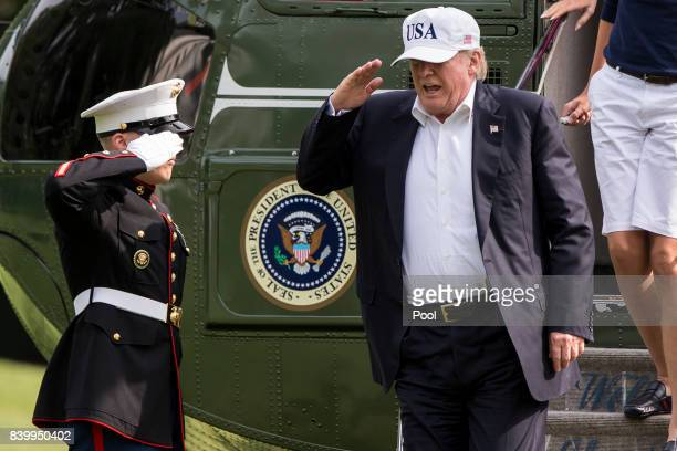 President Donald J Trump salutes as he exits Marine One on the South Lawn August 27 2017 in Washington DC Trump is returning to the White House after...