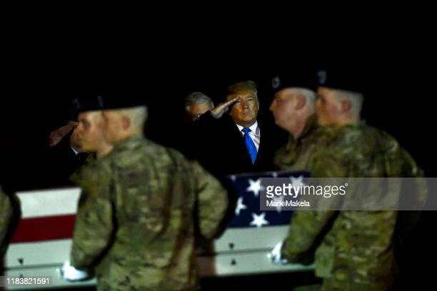 S President Donald J Trump salutes as military personnel carry a transfer case for fallen service member US Army Chief Warrant Officer 2 Kirk T...