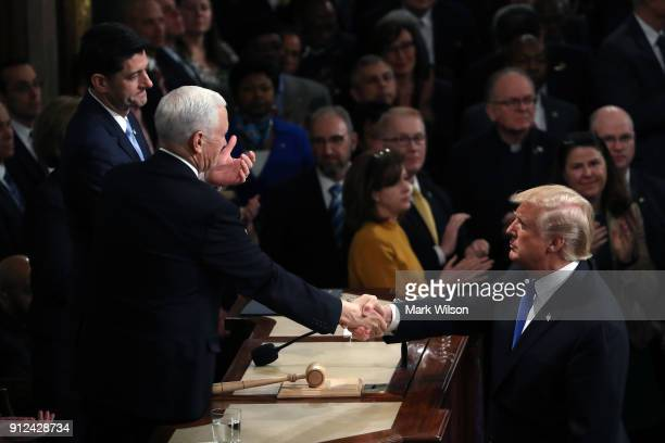 S President Donald J Trump shakes hands with US Vice President Mike Pence during the State of the Union address in the chamber of the US House of...