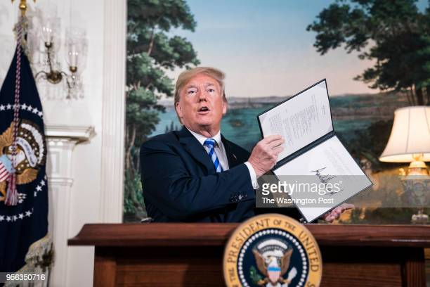 President Donald J Trump signs a National Security Presidential Memorandum as he announces the withdrawal of the United States from the Iran nuclear...