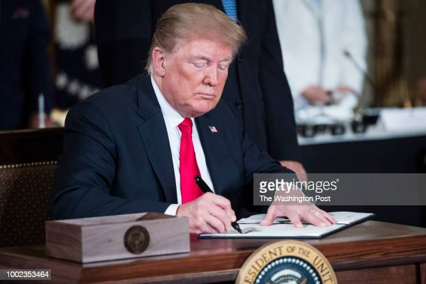 President Donald J Trump signs a Space Policy Directive during a National Space Council meeting in the East Room at the White House on Monday June 18...