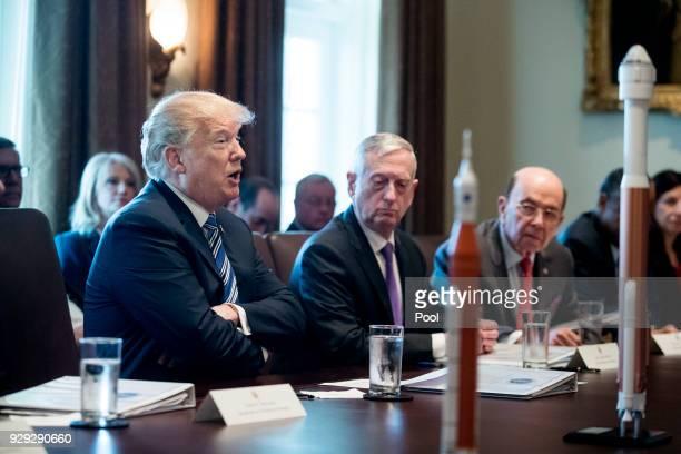 US President Donald J Trump speaks beside US Secretary of Defense Jim Mattis and US Commerce Secretary Wilbur Ross with rocket models seen on the...