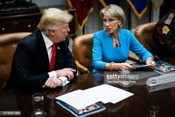 President Donald J Trump speaks with Secretary of Education Betsy DeVos at a roundtable with family members of victims state and local officials and...