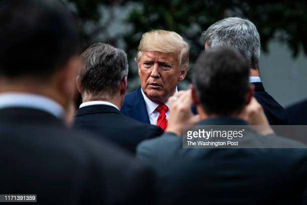 President Donald J Trump talks to others as he walks back to the Oval Office after sheriffs presented him with an appreciation plaque at the South...