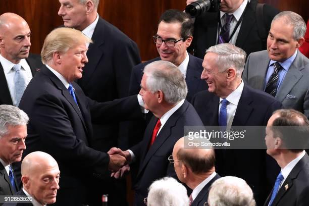 President Donald J. Trump talks with members of his cabinet, including Treasury Secretary Steven Mnuchin, Secretary of State Rex Tillerson, Defense...