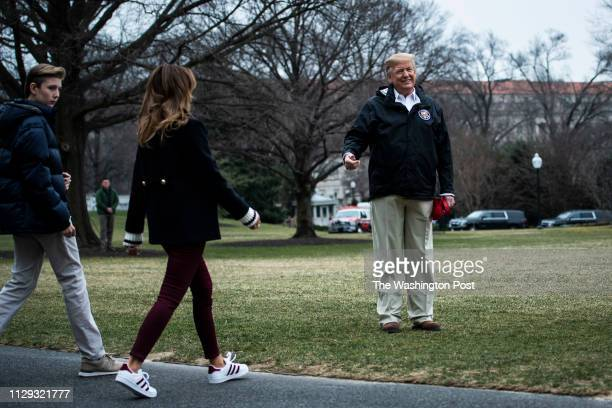President Donald J Trump waits for First Lady Melania Trump and son Barron Trump as they walk to Marine One to depart from the South Lawn at the...