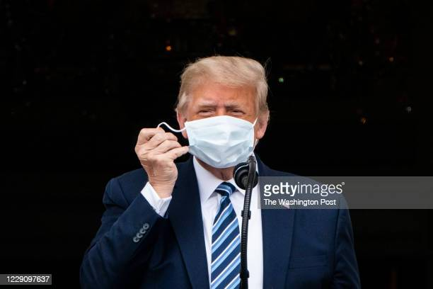 President Donald J. Trump, with a bandage in his hand, removes his face mask as he arrives to speak to supporters from the Blue Room balcony during...