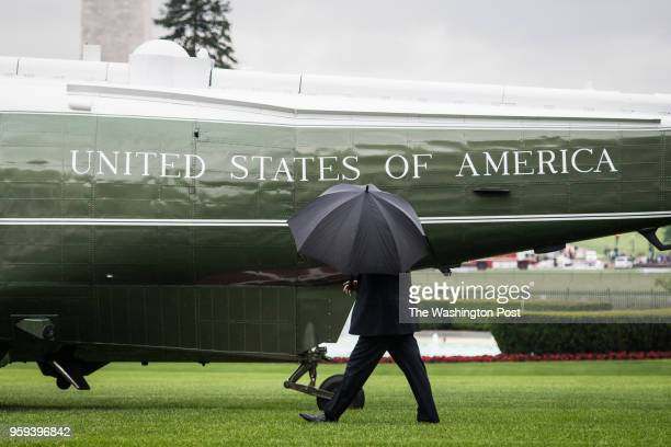 President Donald J Trump with an umbrella walks from the Oval Office to the Marine One helicopter as he departs heading to Walter Reed National...