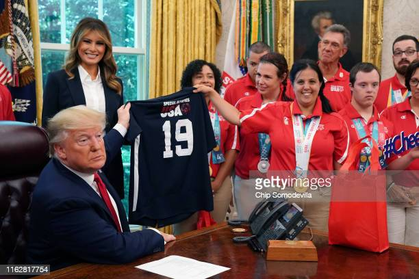 President Donald Trump accepts a jersey from members of the United States Special Olympics World Games team while he and first lady Melania Trump...
