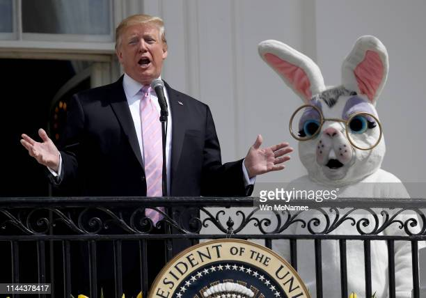 S President Donald Trump accompanied by a person dressed as the Easter Bunny welcomes guests with opening remarks during the 141st Easter Egg Roll on...