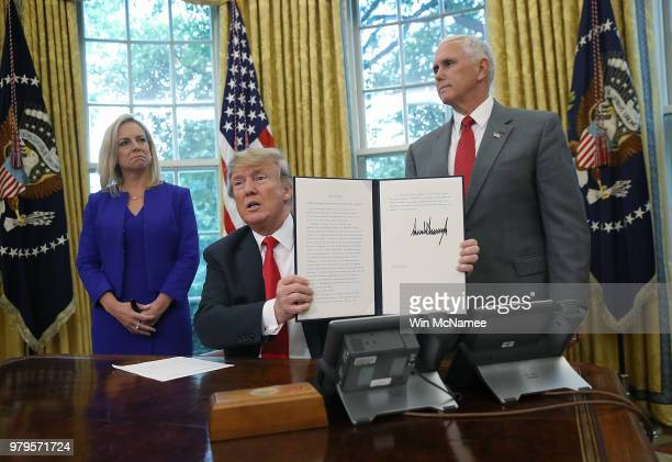 S President Donald Trump accompanied by Department of Homeland Security Secretary Kirstjen Nielsen and US Vice President Mike Pence displays an...