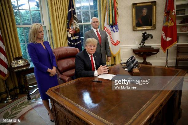 S President Donald Trump accompanied by Department of Homeland Security Secretary Kirstjen Nielsen and US Vice President Mike Pence prepares to sign...