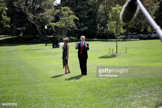 President Donald Trump accompanied by first lady Melania Trump shouts to reporters while departing the White House for Camp David September 8 2017 in...