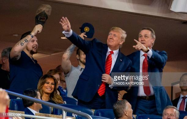 President Donald Trump accompanied by Senator David Perdue and a member of the military stand as members of the military are recognized during Game 5...
