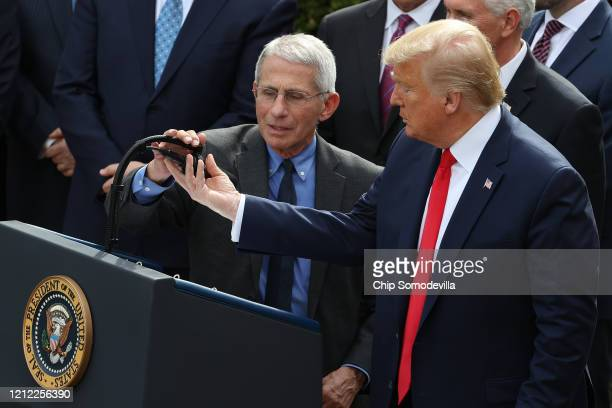 President Donald Trump adjusts the microphone for National Institute Of Allergy And Infectious Diseases Director Anthony Fauci during a news...