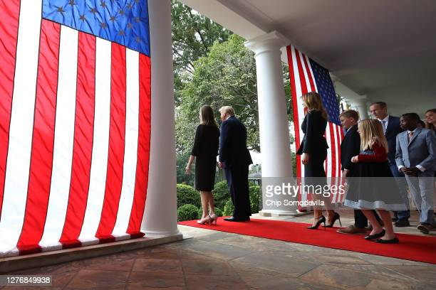 President Donald Trump and 7th U.S. Circuit Court Judge Amy Coney Barrett walk into the Rose Garden with first lady Melania Trump and Barrett's...