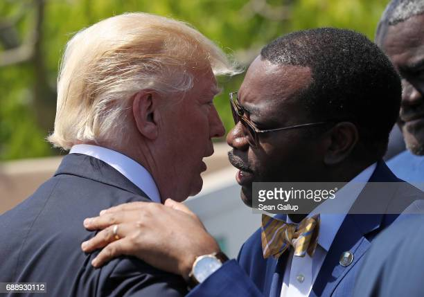 S President Donald Trump and Akinwumi Adesina President of the African Development Bank chat following the group photo for the G7 Outreach Program on...
