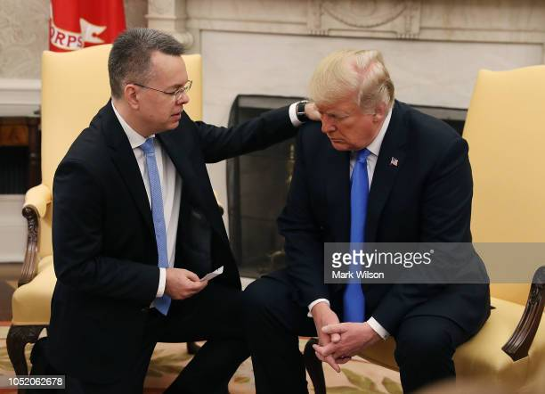 S President Donald Trump and American evangelical Christian preacher Andrew Brunson participate in a prayer in the Oval Office a day after he was...