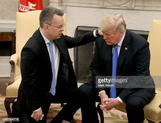 S President Donald Trump and American evangelical Christian preacher Andrew Brunson participate in a prayer in the Oval Office a day after Brunson...