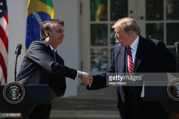 S President Donald Trump and Brazilian President Jair Bolsonaro shake hands during a joint news conference at the Rose Garden of the White House...