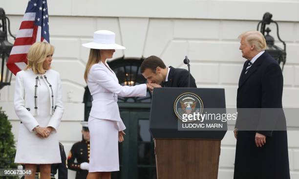 President Donald Trump and Brigitte Macron watch as French President Emmanuel Macron kisses the hand of US First Lady Melania Trump during a state...