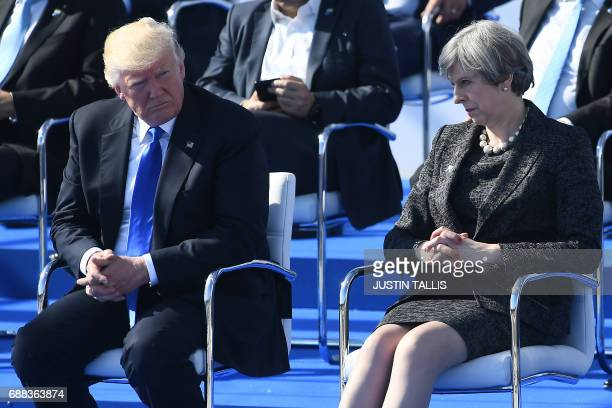 US President Donald Trump and Britain's Prime Minister Theresa May look on during the NATO summit ceremony at the NATO headquarters in Brussels on...