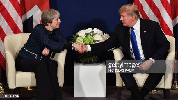 US President Donald Trump and Britain's Prime Minister Theresa May shake hands during a bilateral meeting on the sidelines of the World Economic...