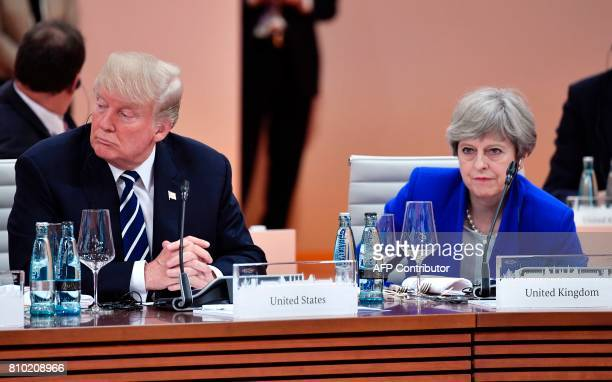 US President Donald Trump and Britain's Prime Minister Theresa May wait at the start of the first working session of the G20 meeting in Hamburg...