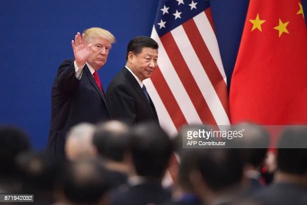 President Donald Trump and China's President Xi Jinping leave a business leaders event at the Great Hall of the People in Beijing on November 9,...