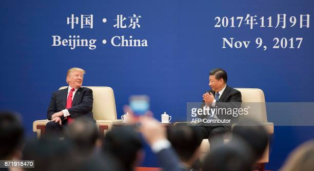 US President Donald Trump and Chinese President Xi Jinping attend a business leaders meeting at the Great Hall of the People in Beijing on November 9...