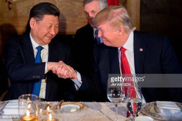 President Donald Trump and Chinese President Xi Jinping shake hands during dinner at the MaraLago estate in West Palm Beach Florida on April 6 2017 /...