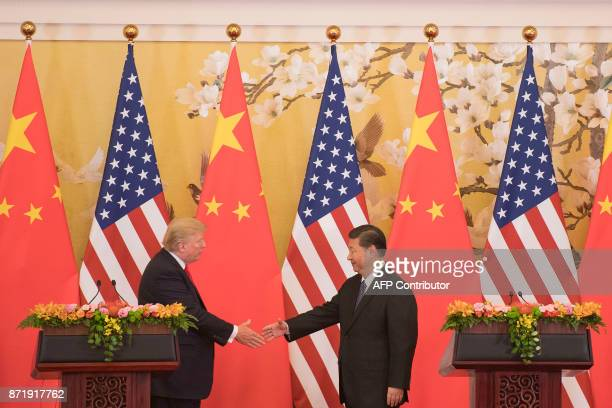 US President Donald Trump and Chinese President Xi Jinping shake hands during a joint statement in Beijing on November 9 2017 Donald Trump and Xi...