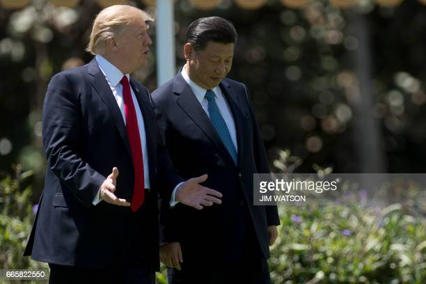 President Donald Trump and Chinese President Xi Jinping walk together at the Mar-a-Lago estate in West Palm Beach, Florida, April 7, 2017.17....