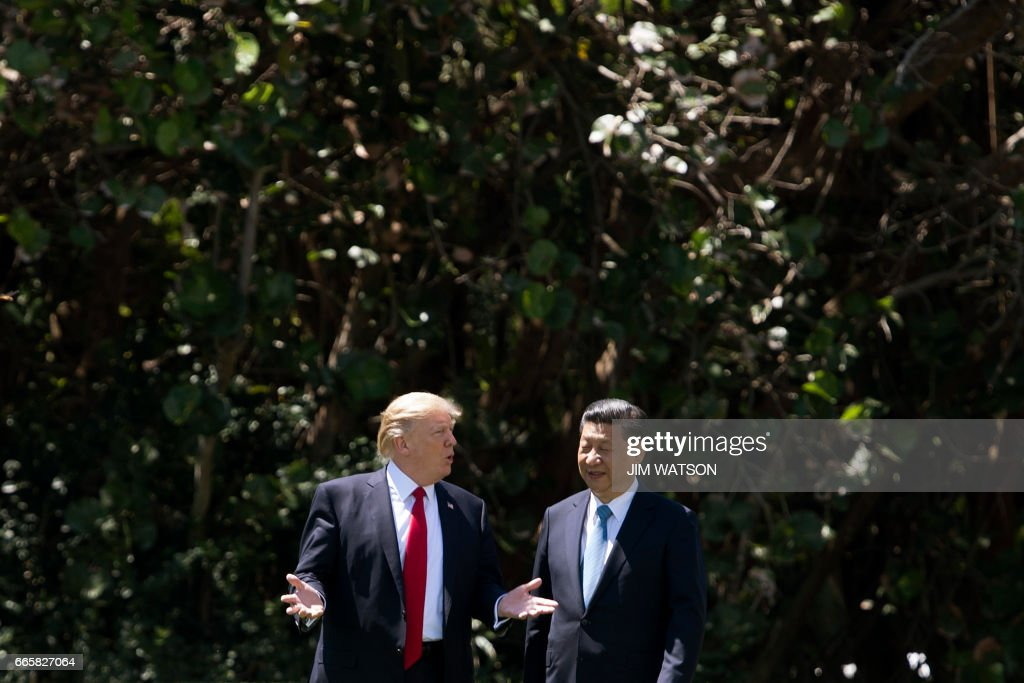 US President Donald Trump (L) and Chinese President Xi Jinping (R) walk together at the Mar-a-Lago estate in West Palm Beach, Florida, April 7, 2017. President Donald Trump entered a second day of talks with his Chinese counterpart Xi Jinping on Friday hoping to strike deals on trade and jobs after an overnight show of strength in Syria. /