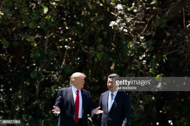US President Donald Trump and Chinese President Xi Jinping walk together at the MaraLago estate in West Palm Beach Florida April 7 2017 President...