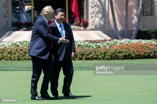US President Donald Trump and Chinese President Xi Jinping walk together at the MaraLago estate in West Palm Beach Florida April 7 2017 / AFP PHOTO /...