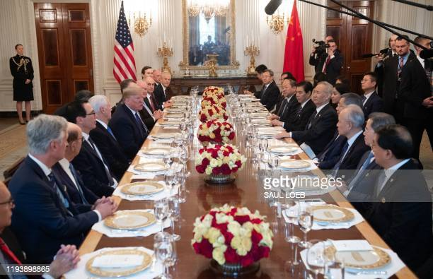 President Donald Trump and Chinese Vice Premier Liu He sit alongside their delegations for a lunch in the State Dining Room after signing a trade...