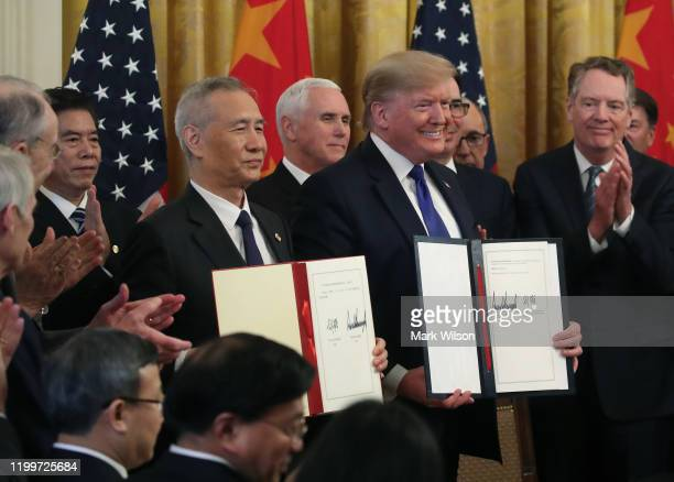S President Donald Trump and Chinese Vice Premier Liu He hold up signed agreements of phase 1 of a trade deal between the US and China in the East...