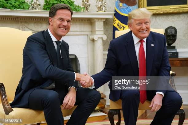 S President Donald Trump and Dutch Prime Minister Mark Rutte pose for photographs after talking to reporters in the Oval Office at the White House...