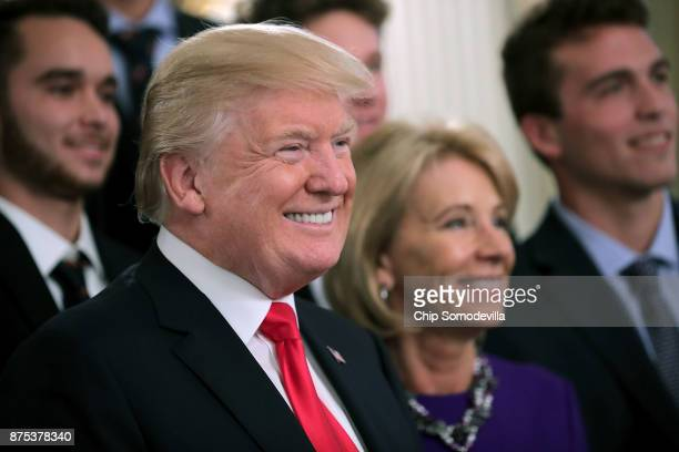 US President Donald Trump and Education Secretary Betsy Devos pose for photographs with members of the National Collegiate Athletic Association's...