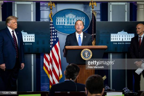 President Donald Trump and FDA Commissioner Stephen Hahn looks on as Health and Human Services Secretary, Alex Azar, addresses the media during a...