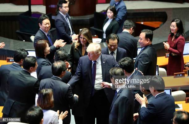 US President Donald Trump and First Lady Melania shake hands with lawmakers as they leave after his speech at the National Assembly in Seoul on...