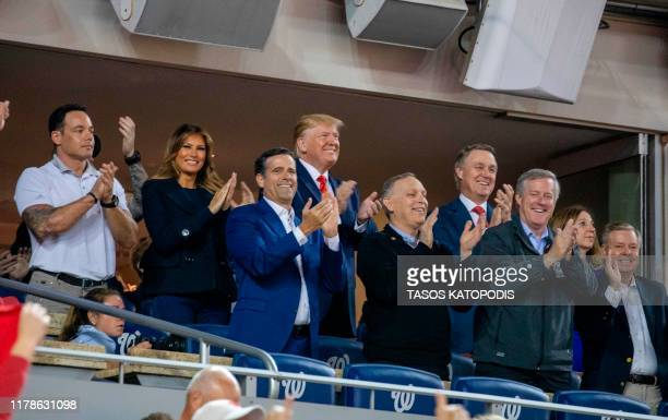 US President Donald Trump and First Lady Melania Trump accompanied by Republican lawmakers and members of the military stand as members of the...