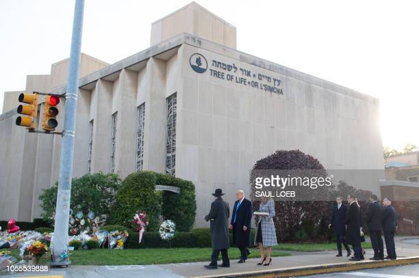 US President Donald Trump and First Lady Melania Trump alongside Rabbi Jeffrey Myers walk to place stones and flowers on a memorial as they pay their...