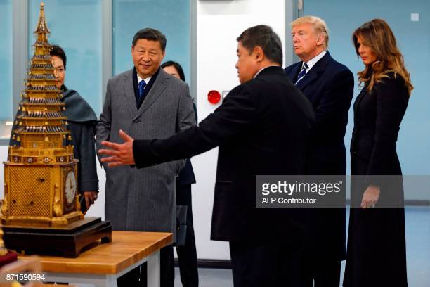 US President Donald Trump and First Lady Melania Trump and China's President Xi Jinping and his wife Peng Liyuan look at an 18th century clock with...