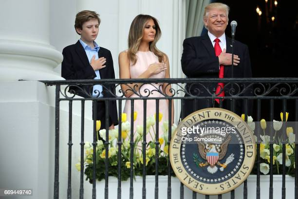 S President Donald Trump and first lady Melania Trump and their son Barron Trump put their hands over their hearts as the Star Spangled Banner is...