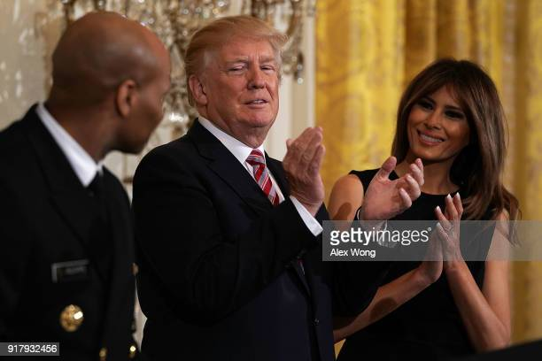 S President Donald Trump and first lady Melania Trump applaud as Surgeon General Jerome Adams looks on during a reception in the East Room of the...