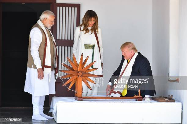 US President Donald Trump and First Lady Melania Trump are accompanied by India's Prime Minister Narendra Modi as they visit the Gandhi Ashram in...