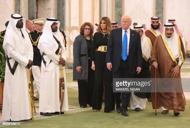 US President Donald Trump and First Lady Melania Trump are escorted by Saudi Arabia's King Salman bin Abdulaziz alSaud as they arrive at the Saudi...