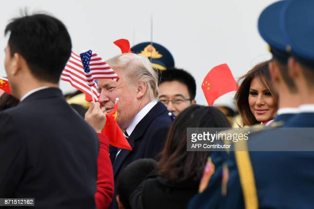 US President Donald Trump and First Lady Melania Trump are greeted as they arrive in Beijing on November 8 2017 US President Donald Trump arrived in...